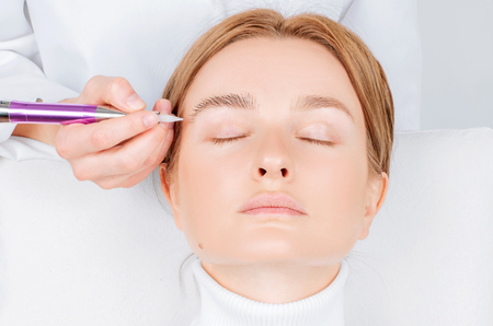 Microblading eyebrows. Cosmetologist making permanent makeup. Attractive woman getting facial care and microblading 版權商用圖片