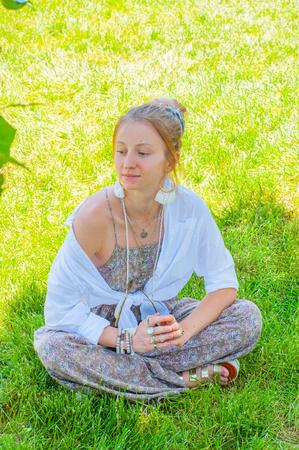 Belle femme de style bohème avec accessoires, bagues et bracelets profitant d'une journée ensoleillée d'été dans le parc. Fille hippie bohème est assise sur l'herbe