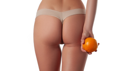 Slim woman is holding orange. Perfect female buttocks without cellulite. Beautiful woman's butt in underwear. Body care and anti cellulite massage Standard-Bild - 124369356