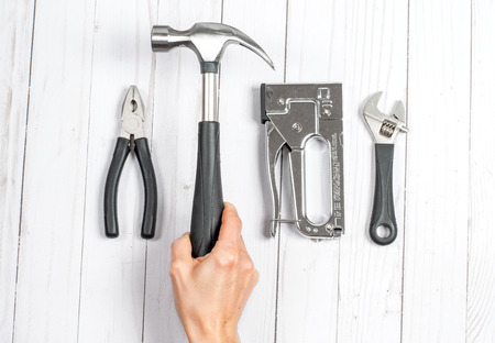 Hand holding hammer. Tools, wrenches and pliers on a white wooden background