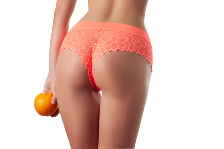 Skin care and anti cellulite massage. Perfect female buttocks without cellulite in panties. Beautiful woman's butt in underwear. Slim fit woman body with orange. Standard-Bild - 124369438