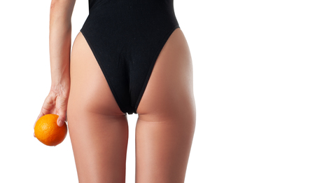Skin care and anti cellulite massage. Perfect female buttocks without cellulite in panties. Beautiful woman's butt in underwear. Slim fit woman body with orange. Standard-Bild - 124369446