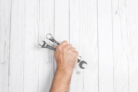 Tool. Hand  is holding wrenches isolated on white wooden background.