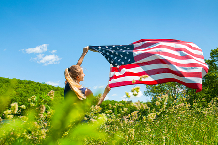 United States flag. Young woman holding American flag outdoors. 4th of July