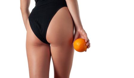 Huidverzorging en anti cellulitis massage. Perfecte vrouw zonder cellulitis in slipje. De kont van de mooie vrouw in ondergoed. Slim fit vrouwenlichaam met oranje. Stockfoto