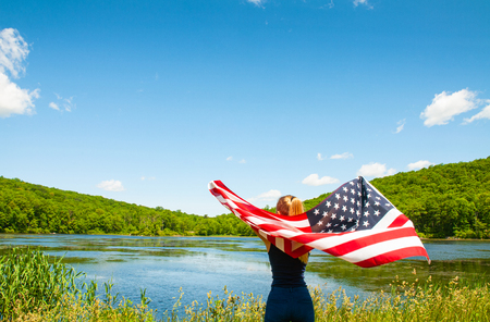Young woman holding American flag on lake background. United States celebrate 4th of July
