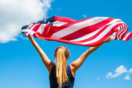 Young woman holding American flag on blue sky background. United States celebrate 4th of July