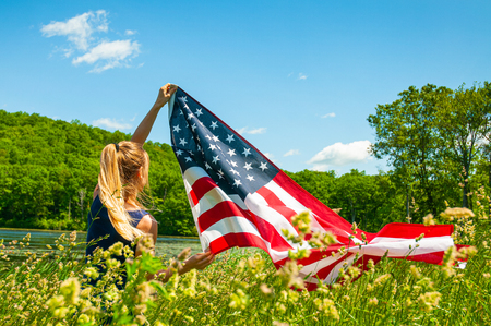 Young woman holding American flag outdoors. United States celebrate 4th of July Independence Day. 版權商用圖片
