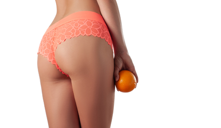 Skin care and anti cellulite massage. Perfect female buttocks without cellulite in panties. Beautiful womans butt in underwear. Slim fit woman body with orange.