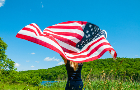 Beautiful young woman holding American flag on blue sky background