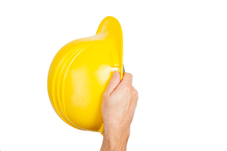 Tool. Hand in glove is holding yellow safety helmet isolated on white background.