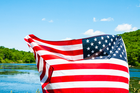 American flag on lake background. United States celebrate Independence Day. Patriotic holiday 4th of July.