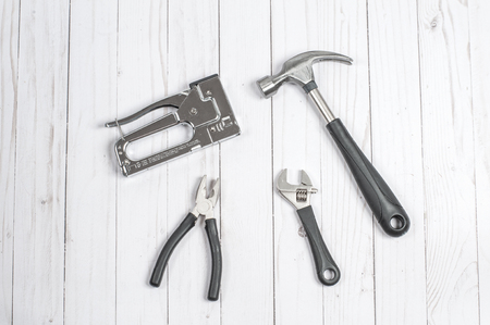 Tools. Wrenches, hammer and pliers on a white wooden background