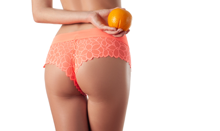 Skin care and anti cellulite massage. Perfect female buttocks without cellulite in panties. Beautiful woman's butt in underwear. Slim fit woman body with orange. Standard-Bild - 124369646