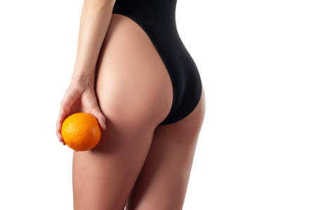 Skin care and anti cellulite massage. Perfect female buttocks without cellulite in panties. Beautiful woman's butt in underwear. Slim fit woman body with orange. Standard-Bild - 124369767