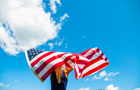 Young woman holding American flag on blue sky background. Independence Day. United States celebrate 4th of July 版權商用圖片