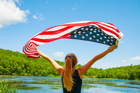 Independence Day. Young woman holding American flag on lake background. United States celebrate 4th of July