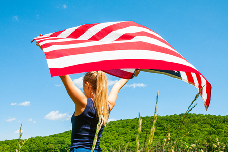 4th of July. Young woman holding American flag on blue sky background.