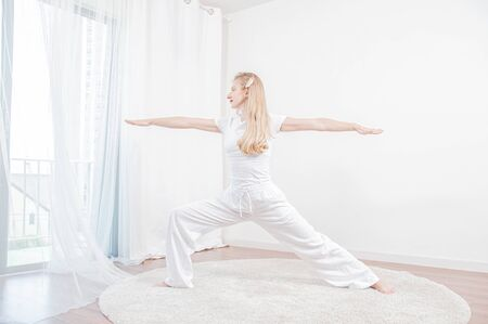 Yoga time. Beautiful woman is practicing yoga at home, girl doing Virabhadrasana exercise, standing in Warrior pose