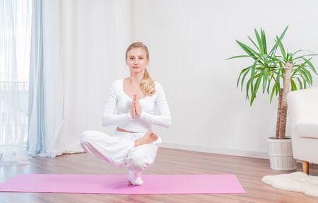 Beautiful woman is practicing yoga at home on yoga mat, girl doing Half Lotus Toe Balance exercise, Sitting in squat position