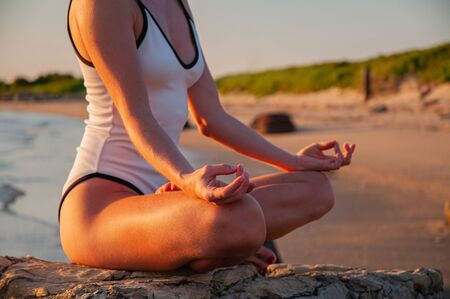 Woman is meditating on the calm beach at sunset. Woman is practicing yoga sitting in Lotus pose at sunrise. Silhouette of woman meditating on the beach Stock fotó