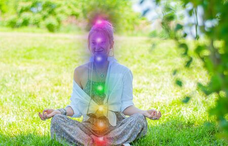 Happy woman is meditating in the lotus pose with glowing seven chakras on grass. Woman is practicing yoga on the park. Kundalini meditation. Stock fotó