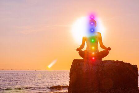Frau meditiert mit leuchtenden sieben Chakren auf Stein bei Sonnenuntergang. Silhouette der Frau praktiziert Yoga bei Sonnenuntergang am Strand. Kundalini-Meditation.