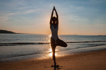 Silhouette woman yoga on the beach at sunset. Woman is practicing yoga at sunset on sea coast. Calm and self control.