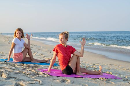 Young women practicing yoga on the beach. Beautiful girls practicing yoga at seashore.