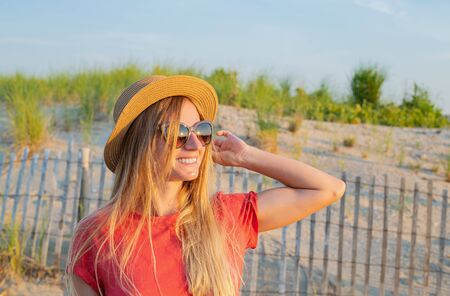Beautiful woman in summer hat on the beach near wooden fence. Travel and vacation.