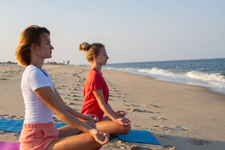Title: Young women practicing yoga on the beach at sunset. Girls meditating, sitting in lotus pose on the sea shore. Imagens
