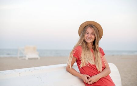 Beautiful woman with long blond hair wear straw hat on the beach near wooden boat. Travel and vacation.