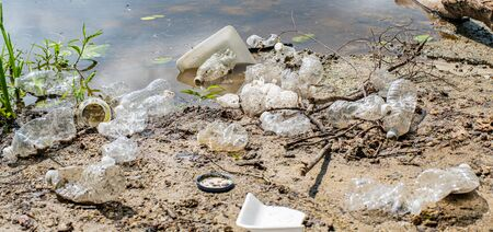 Trash and used plastic bottles in the river. Garbage near lake. Environmental pollution. Ecological problem Stock fotó