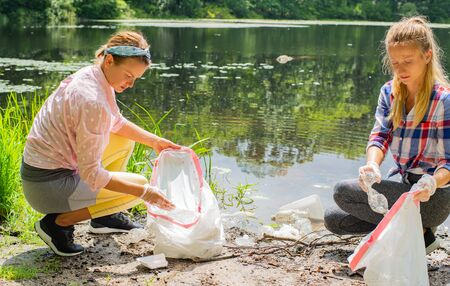 Volunteers cleaning garbage near river. Women picking up a bottle plastic in the lake, pollution and environment. Ecology concept Фото со стока