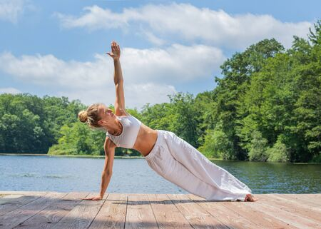Attractive young woman is practicing yoga, doing Camatkarasana pose near lake in morning.