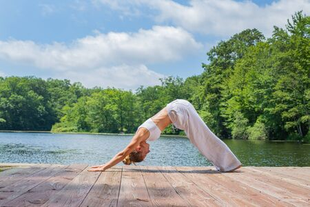 Attractive young woman is practicing yoga, doing Adho Mukha Svanasana exercise, standing in Downward facing dog pose near lake in morning.