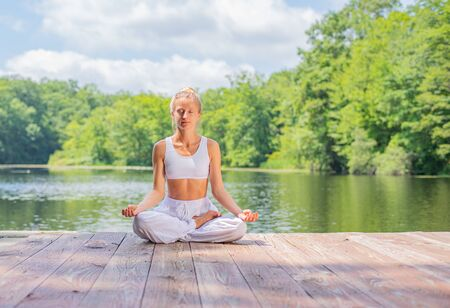 Attractive woman is practicing yoga and meditation sitting in lotus pose near lake. Young woman is meditating outdoors in morning.