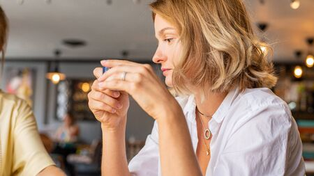 Beautiful woman sitting in a cafe with a cup of coffee. Attractive young woman is drinking coffee in the morning at cafe