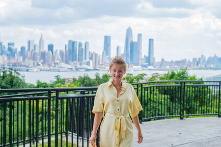 Attractive young woman in dress, looking to the camera and smiling on New York City background. Banco de Imagens