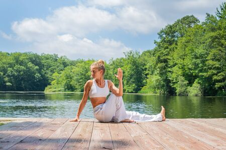 Attractive woman is practicing yoga sitting in Ardha Matsyendrasana pose near lake. Young woman is meditating outdoors in morning.
