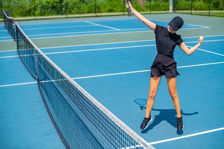 Young tennis player woman celebrating victory in match point. Happy tennis woman winner celebration of success and win.