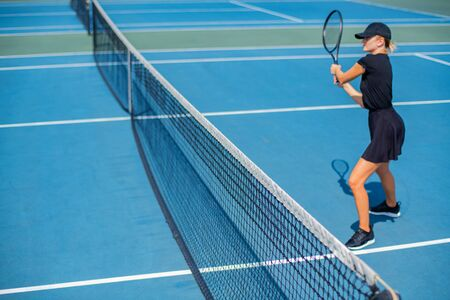 Beautiful sports woman playing tennis on the blue tennis court Imagens