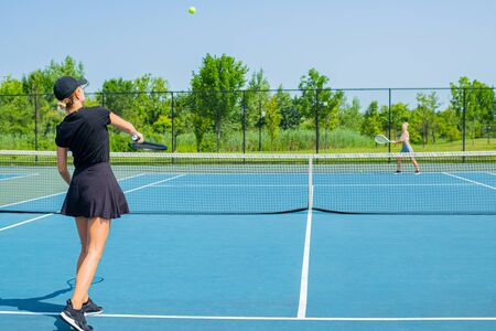 Two young sports women playing tennis on the blue tennis court