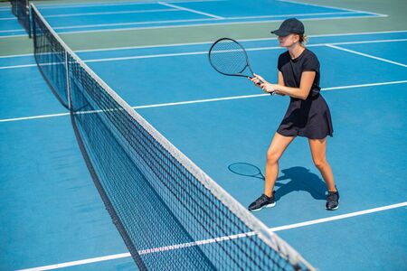 Beautiful sports woman playing tennis on the blue tennis court Фото со стока