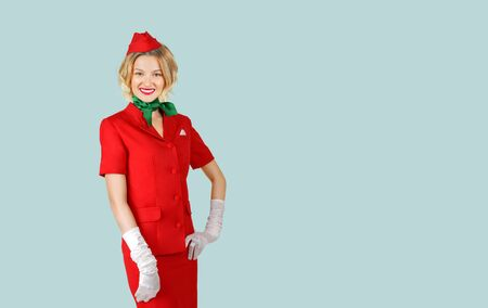 Portrait of charming stewardess wearing in red uniform on gray background. Stockfoto
