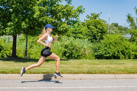 Sporty young woman in sportswear trail running on the road. Beautiful athlete girl is jogging in the park.