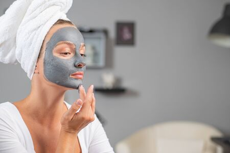 Beautiful woman is applying facial clay mask. Beauty treatments and skincare, woman getting facial cleansing mask at home