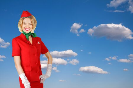 Portrait of charming stewardess wearing in red uniform on sky background.