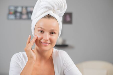 Happy young woman applying cream to her face. Cosmetics. Woman face skin care.