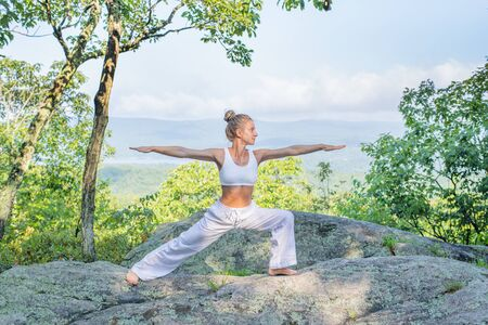 Young woman practicing yoga outdoors harmony with nature. Girl doing yoga standing on stone in Warrior pose